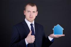 Casetta della tenuta dell'uomo di affari sulla suoi mano e pollici su Immagine Stock