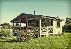 Casetta di legno di estate con un letto di fiore fotografia stock