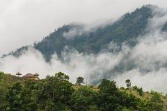 Casetta sulla montagna con nebbia e la nuvola Fotografie Stock