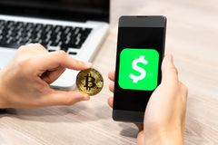Cash App logo by Square inc displayed on smartphone held by human hand next to Bitcoin coin and computer laptop - stock images