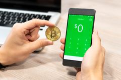 Cash App by Square inc displayed on smartphone held by human hand next to Bitcoin coin and computer laptop - Slovenia 13 royalty free stock photos