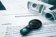 Cash and auto insurance policy. Car insurance policy with money and key fob Royalty Free Stock Image