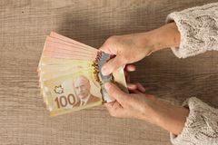 Cash bills from Canadian currency. Dollars. Above view of old re. Tired person paying in cash royalty free stock image