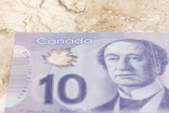 Cash bills from Canadian currency. Dollars. Closeup on marble ta. Ble royalty free stock photo