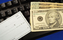 Cash and check on a keyboard royalty free stock image