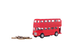 Cash coins with a model red double-decker bus. Symbolic of British transport and the cost of travelling isolated on white Royalty Free Stock Photography