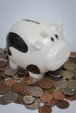 Cash Cow. Porcelain cow on top of cash coins, demonstrating concept of 'cash cow Royalty Free Stock Photography