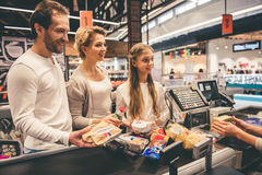 At the cash desk. Beautiful parents and their daughter are smiling while standing at the cash desk in supermarket Stock Photos