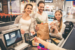 At the cash desk. Beautiful parents and their daughter are smiling while standing at the cash desk in supermarket Royalty Free Stock Photo