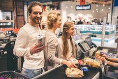 At the cash desk. Beautiful parents and their daughter are smiling while standing at the cash desk in supermarket Royalty Free Stock Photos