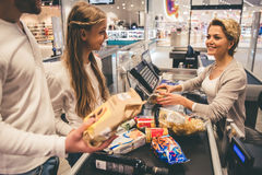At the cash desk. Dad and daughter at the cash desk in supermarket, beautiful cashier is smiling Stock Photos