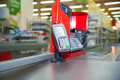 Cash desk with payment terminal in supermarket. Empty cash desk with payment terminal and customers in queue in supermarket Stock Photography
