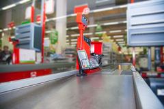 Cash desk with payment terminal in supermarket. Empty cash desk with payment terminal and customers in queue in supermarket Stock Photo