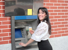 Cash dispenser. Beautiful smiling woman withdrawing some money from a cash dispenser Royalty Free Stock Photography