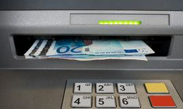 Cash dispenser with Euros. Euro notes coming out of the hole in the wall, cash dispenser machine. Spending concept Royalty Free Stock Photography