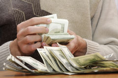 Cash dollars in hands Stock Images