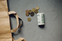 Cash dollars money, euro coins with a Kraft package on gray stock image