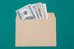 Cash in an envelope. On a green background Royalty Free Stock Images