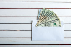 Cash in an envelope on white wooden table. Royalty Free Stock Images