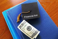 Financial Aid money. Cash and Financial Aid graduation cap on school books Royalty Free Stock Photography