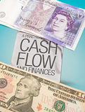 Cash flow. A sign offering help with cash flow and with Pounds and Dollar bills above and below it. An abstract image of money flowing into and out of companies Royalty Free Stock Image