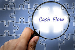 Cash flow word. Magnifier and puzzles. Stock Photo
