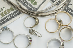 Cash For Gold. Antique gold and white gold rings, and a silver necklace laying with 100 dollar bills royalty free stock photos