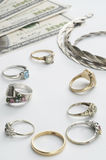 Cash For Gold. Antique gold and white gold rings, and a silver necklace laying with 100 dollar bills stock photo