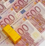 Cash and gold. Gold bar with 500 euro banknotes royalty free stock photos