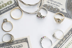 Cash for gold. Rings and a necklace pictured with 100 dollar bills stock images