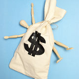 Cash Grab. A dummy is crushed by a large bag of money Royalty Free Stock Images