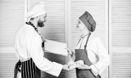 Cash in hand. Master cook and helper holding account book and cash money. Cook helper giving cooking worksheet to chef stock photo