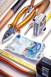 Cash and hand tools. A twenty euro bill with various hand tools around it Stock Photo