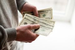 Cash in hands. Profits, savings. Stack of dollars. Man counting money. Dollars in man`s hands. Success, motivation, financial royalty free stock photos