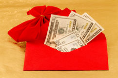 Cash, The Holiday Gift of Choice. Cash gift of dollars is in red envelope with red velvet bow accent against gold paper to show the holiday gift of choice Stock Photo