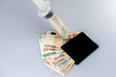 Cash injection. Wallet with money, a syringe injecting money into it Royalty Free Stock Photos