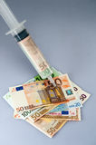 Cash injection. A syringe filled with money is injecting money Royalty Free Stock Images