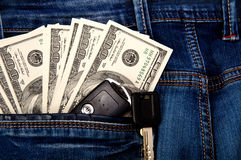 Cash and key from the car in pocket. Dollars and key from the car in the back pocket of jeans Stock Photos