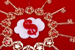 Cash keys. Red dollar sign shape made of plexiglas lie inside of a white cloud shape with a golden skeleton keys around on a red background Royalty Free Stock Photo
