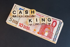 Cash is King. Text ' Cash is King ' in black upper case letters on small white cubes placed on a pile of Euros  isolated on dark background Stock Images