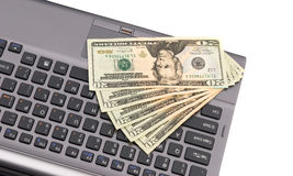 Cash on laptop keyboard. Stock Photo