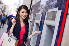 Cash machine. Happy young chinese girl at the cash machine Stock Photos