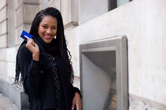 Cash machine. A happy young woman holding a cash card at a cash mashine Stock Photography