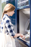 Cash machine. Woman at the cash machine putting her pin in Royalty Free Stock Photo
