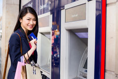 Cash machine. Young chinese girl at the cash machine Royalty Free Stock Photography