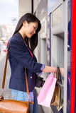 Cash machine. Young chinese girl withdrawing money at the cash point Stock Photo