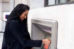 Cash machine. Young woman withdrawing cash at the ATM Stock Photo