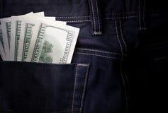 Money in jeans pocket, several hundred-dollar bills. Cash, money is in the back pocket of dark blue men`s jeans Royalty Free Stock Photography