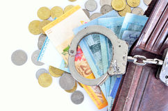 Cash money and handcuffs Stock Photo