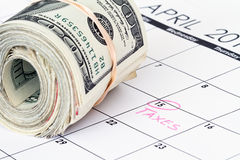 Cash money rolls on a calendar Royalty Free Stock Photo